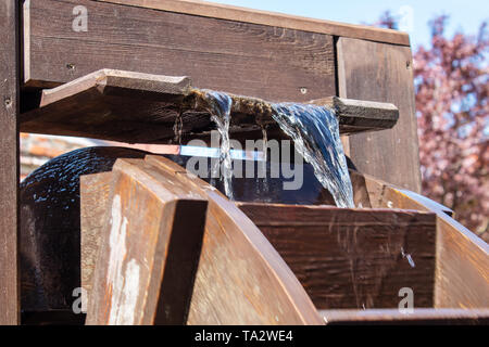 large wooden wheel rotating with water outdoor closeup on sunny day - Stock Image