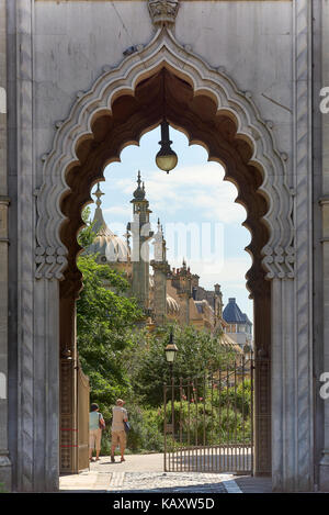 A couple walks into the Brighton Pavilion complex, framed by an archway. - Stock Image