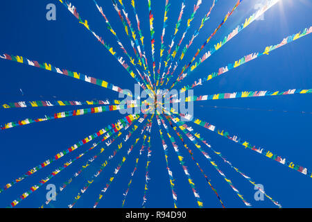 multicolored festoons hanging in blue sky for an event or celebration, with sunbeams - Stock Image