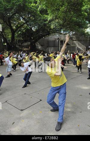 Man and group practising Qigong. Kowloon Park, Tsim Sha Tsui, Kowloon, Hong Kong, China - Stock Image