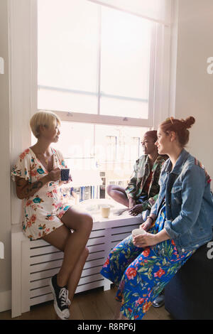Young women friends talking and drinking tea in apartment window - Stock Image