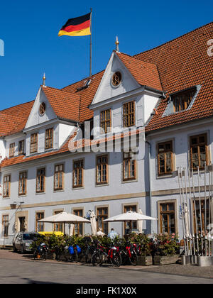 Cyclist sitting outside of old townhall, outside restaurant, Celle, Germany - Stock Image