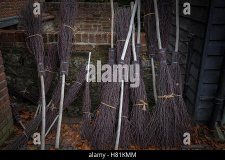 A line of hand made besom brooms. - Stock Image
