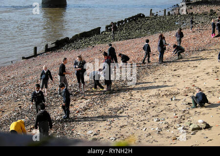 A view of schoolchildren school group mudlarking on the north sandy beach side of the River Thames in winter sunshine London England UK  KATHY DEWITT - Stock Image