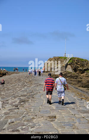Bude, Cornwall, UK. UK Weather. Tourists walk along The Breakwater structure enjoying the hot weather - Stock Image