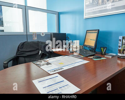 Empty work station or office cubical at a car dealership or office building with a desktop computer. - Stock Image
