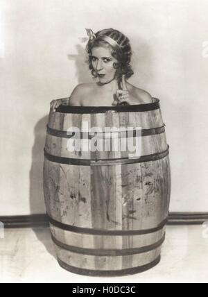 Naked woman sitting in wooden barrel - Stock Image
