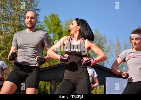 Nis, Serbia - April 20, 2019 Group of attractive people practicing Piloxing sport in an outdoor class in summer with instructor - Stock Image
