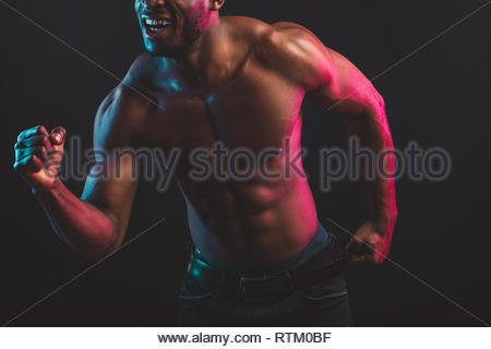Cropped shot of African male athlete showing determination and endurance exercising muscles during fitness photo session isolated over dark background - Stock Image