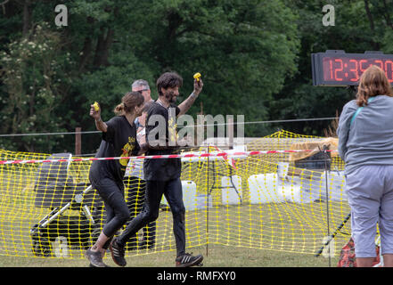 A couple finishing a mud run hold high the duck tokens - Stock Image