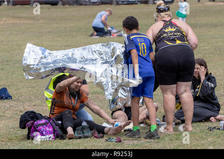 Mud runners are given foil blankets after the event - Stock Image