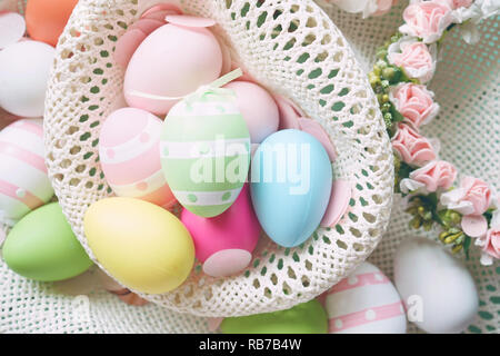 A beautiful and colorful close-up flat of easter eggs in plain colors and striped in a basket with flowers - Stock Image