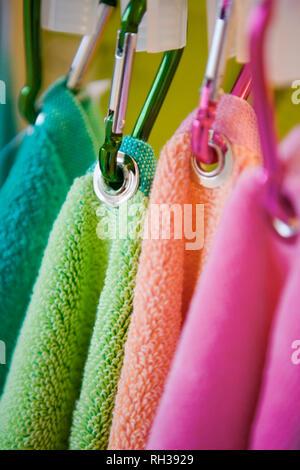 Towels hanging on karabiners - Stock Image