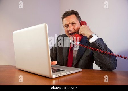 Angry man wearing a suit, shouting down a red telephone while sitting in front of a laptop on a desk. - Stock Image