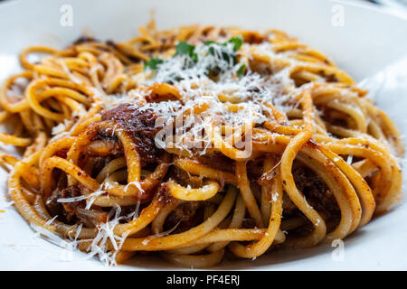 A bowl of spaghetti bolognaise server in a white bowl at an italian restaurant. - Stock Image