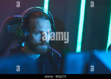 Concentrated zombie gamer with beard wearing headset sitting in front of computer monitor in dark video game club - Stock Image
