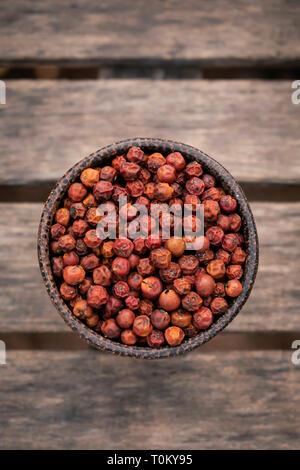 organic kampot dried red pepper corns in cambodia in traditonal asian wood bowl - Stock Image