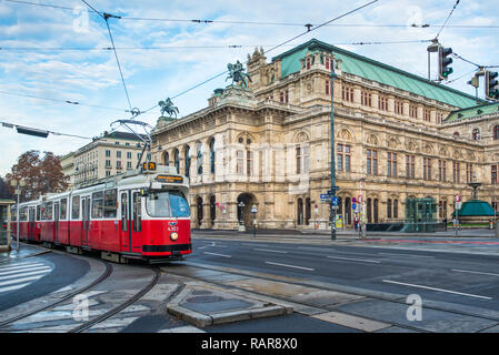 A red tram passes the State Opera House on Ringstrasse, Vienna, Austria. - Stock Image