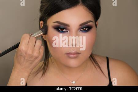 Makeup artist working with Asian model in beauty salon. Face sculpt. Contouring. Make up woman face. Contour and highlight. - Stock Image