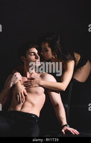 woman in black lingerie standing and hugging shirtless man sitting on couch isolated on black - Stock Image