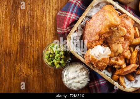 Traditional fish in beer batter and chips served on basket. Top view - Stock Image