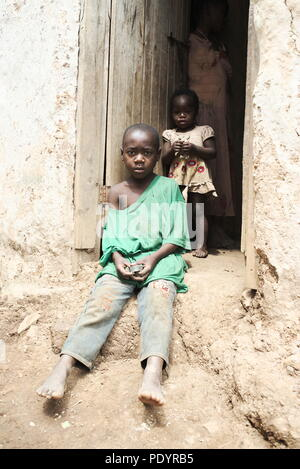 a poor under dressed Young Ugandan child sits in a doorway of a temporary mountain home in Southwest Uganda - Stock Image