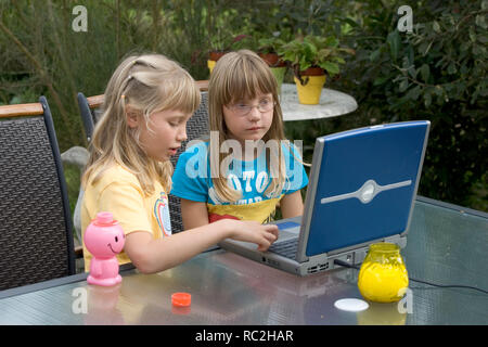 Two young female children in the 2000s playing with a laptop computer in the back garden in summer. - Stock Image