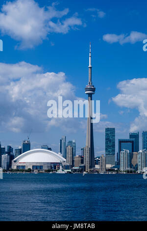 The CN Tower and Rogers Centre Center dominate the Toronto skyline seen from the Toronto Island ferry on a sunny day. Vertical format with copy space. - Stock Image