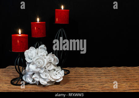 Beautiful bouquie of white roses, red candles perched on black candle holders on mesh place mat and wooden table with card and dark background. Valent - Stock Image