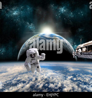 A team of astronauts work on a space station in orbit over a cloud covered world. A neighboring Earth-like planet - Stock Image