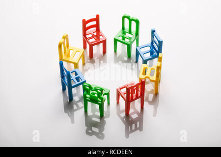A circle of mini plastic chairs - Stock Image