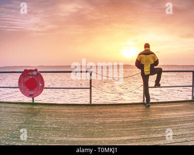 Man thinking. Tourist in warm clothes on sea mole at handrail. Autumn misty day. Tourist on pier in Dranske - Stock Image