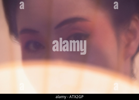 Eyes of Asian woman in 'Kabuki make up' peering through fan - Stock Image