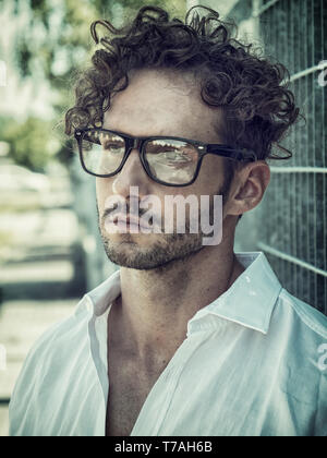 One handsome man in city setting wearing glasses - Stock Image