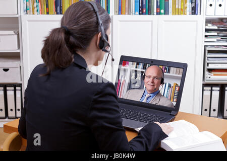 Woman with headset in front of her laptop and a book making an online phone call with a client or colleague, copy - Stock Image