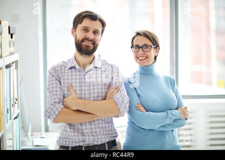 Young successful smiling office staff in casualwear crossing arms on chest while looking at you - Stock Image