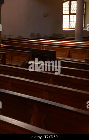 rows of wooden church benches lit by the sun through colored windows, old pews in a church - Stock Image