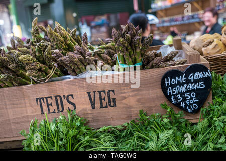 Asparagus home grown in rustic wooden crate at £3.50 pr bunch or 4 for £10 with heart shaped backboard price tag 'Teds Veg' at Borough Market international produce market Southwark London UK - Stock Image