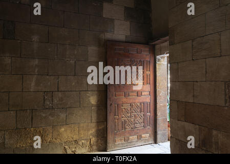 Old abandoned room with stone bricks and grunge weathered wooden decorated door, Old Cairo, Egypt - Stock Image