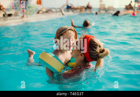 A happy small toddler boy with armbands and his mother swimming in water on summer holiday. - Stock Image