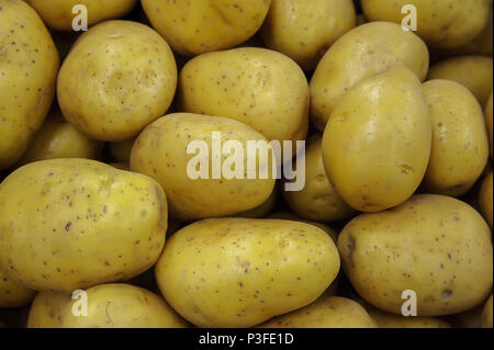 Tasty golden potatoes background displayed on a farmers market stool - Stock Image