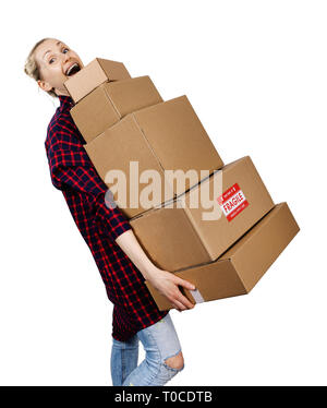 young woman carrying stack of heavy cardboard boxes isolated on white - Stock Image