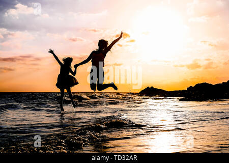 Happy mother and daughter jumping together along the sea water - Silhouette of loving family having fun on the beach - Stock Image