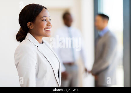 young African American businesswoman in office looking outside the window - Stock Image
