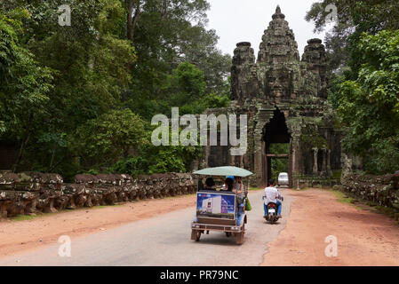 Tuk tuk heading towards one of the many ornate gates in Angkor Wat. The Angkor Wat complex, Built during the Khmer Empire age, located in Siem Reap, C - Stock Image