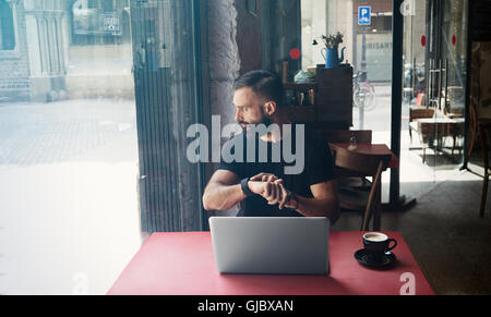 Young Bearded Businessman Wearing Black Tshirt Working Laptop Urban Cafe.Man Sitting Wood Table Cup Coffee Looking - Stock Image