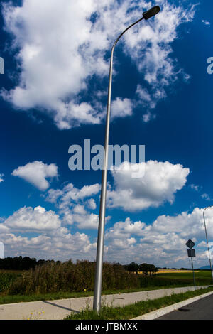 Lamppost next to a road with blue cloudy sky in the background. - Stock Image