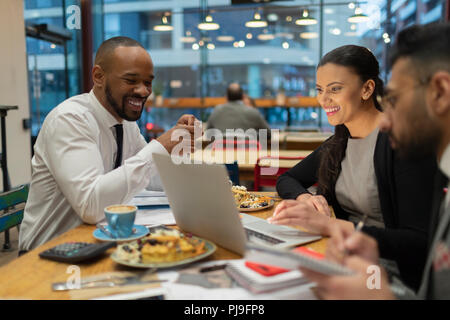 Business people meeting, working at laptop in cafe - Stock Image