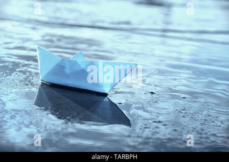 Lonely blue paper boat in shallow water. Blue toned image. - Stock Image
