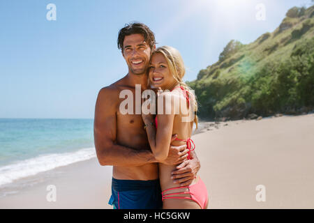 Loving couple in swimsuit embracing on the beach. Romantic young couple on sea shore  looking away and smiling. - Stock Image